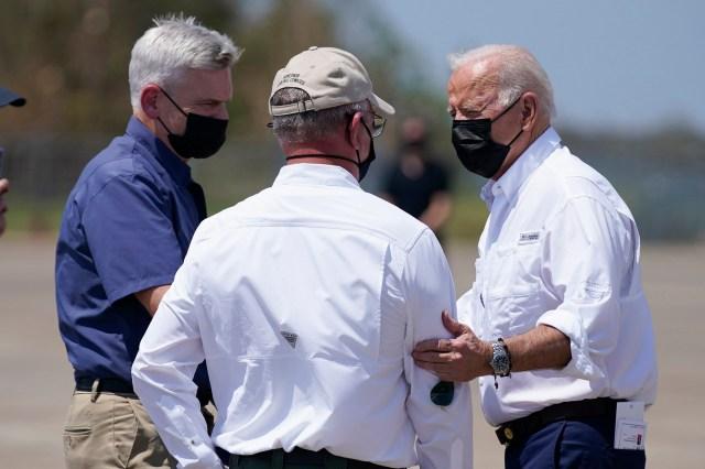 President Biden is seen with notes in his back pocket while greeting La. Gov. John Bel Edwards.