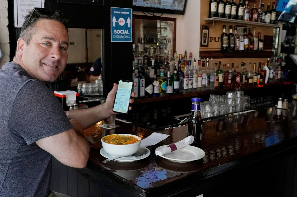 A man showing his COVID-19 vaccine car on his phone while eating at a restaurant in Manhattan on August 17, 2021.