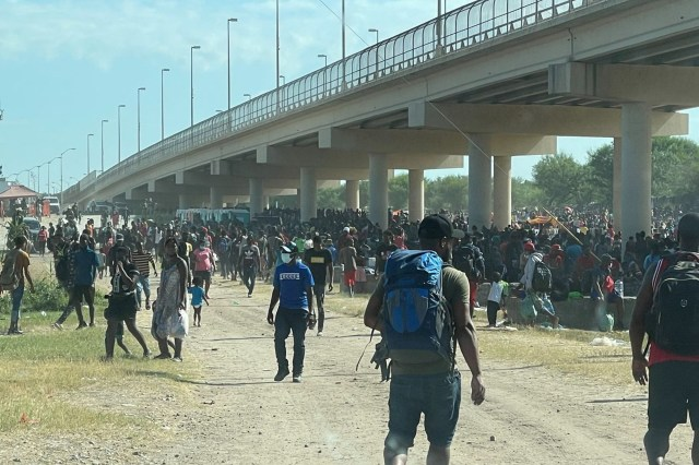 Migrants are seen by the International Bridge between Mexico and the US in Del Rio, Texas.