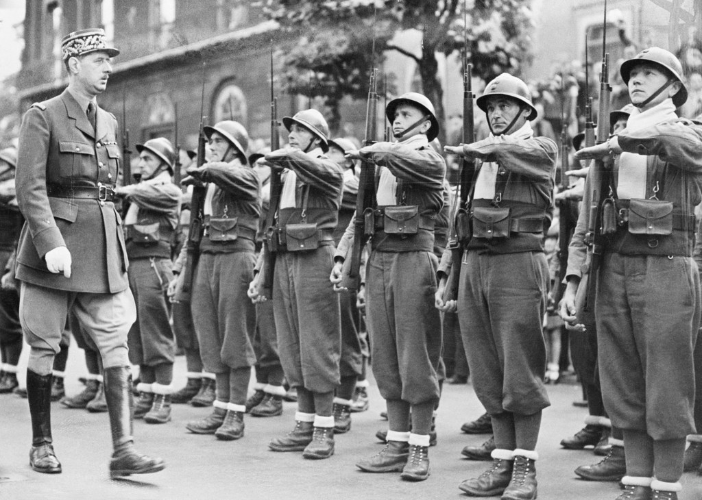 """The fourteenth of July, a national holiday in France, was celebrated in London by these """"free"""" Frenchmen who defied Adolf Hitler and his Nazis in 1940. General de Gaulle, leader of the """"free"""" Frenchmen is shown here inspecting French troops in London on Bastille Day."""