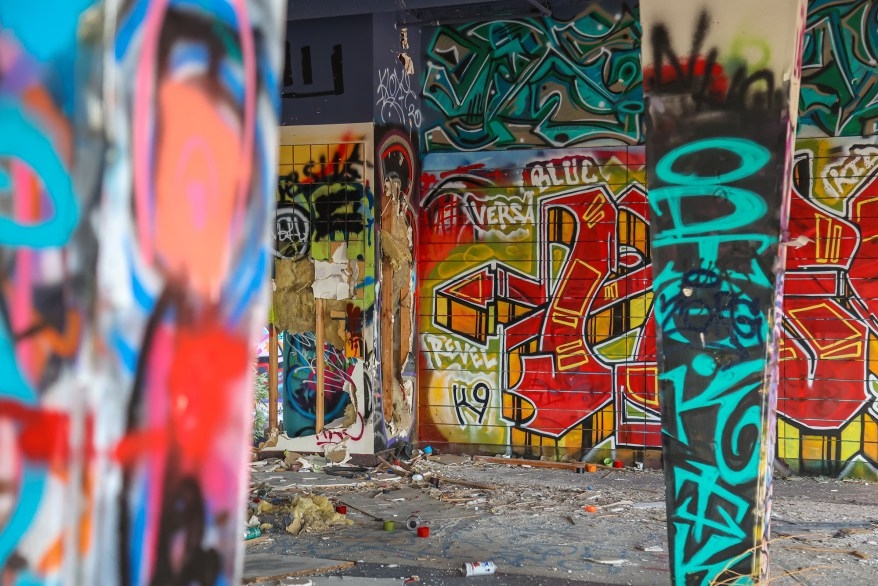 Dirt, overgrown trees, barren stretches of land, graffiti, spray paint cans and litter mark the site in the new photos.