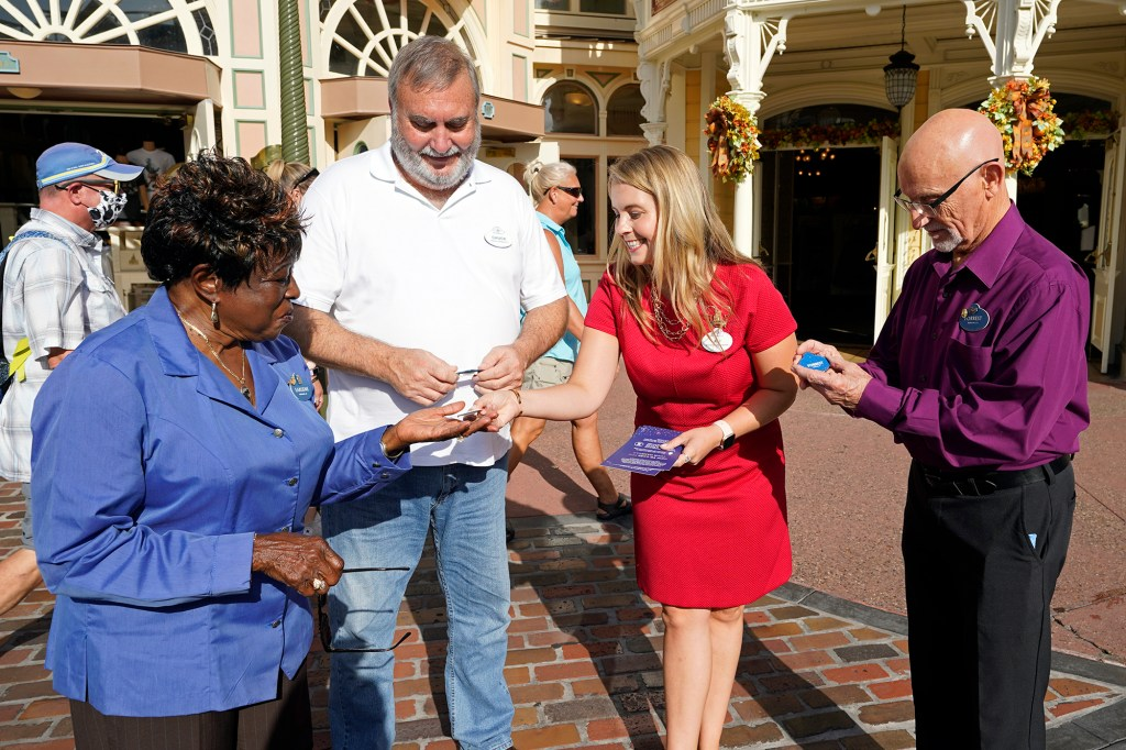 Walt Disney World Ambassador Ali Manion, second from right, presents special 50th Anniversary name tags to employees, from left, Earliene Anderson, Chuck Milam and Forrest Bahruth at the theme park at Monday, Aug. 30, 2021, in Lake Buena Vista, Fla.