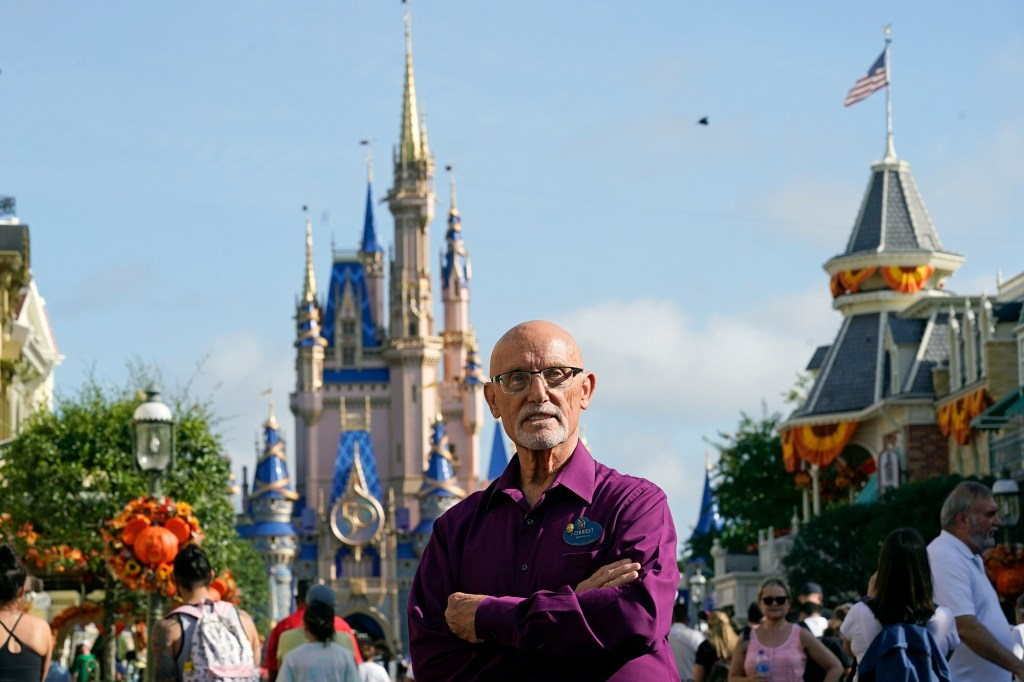 Forrest Bahruth stands on Main Street in front of the Cinderella Castle at the Magic Kingdom theme park at Walt Disney World Monday, Aug. 30, 2021, in Lake Buena Vista, Fla. Bahruth has been working at Disney since the opening day in 1971.