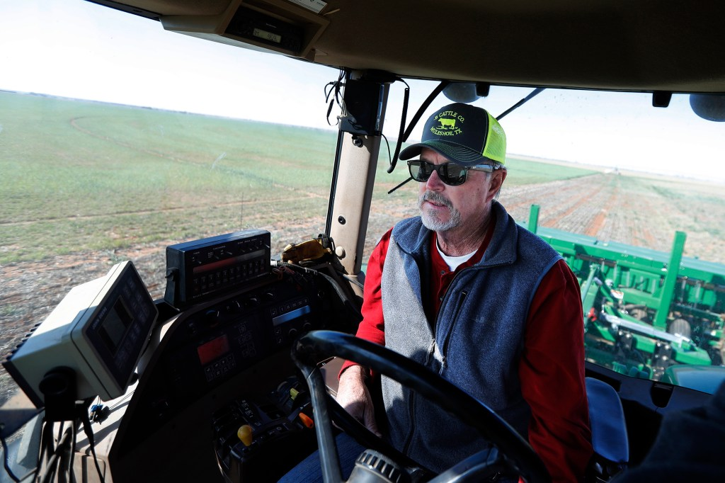 Tim Black uses his tractor's GPS system while planting grass seed on his Muleshoe, Texas, farm on Monday, April 19, 2021.