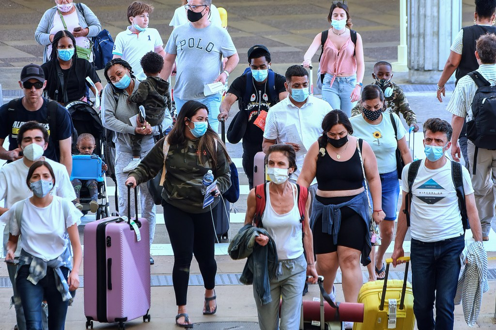 Travelers wearing protective face masks arrive at Orlando International Airport.