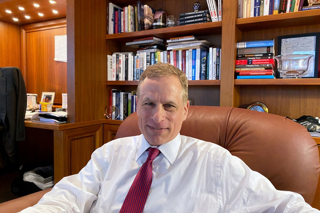 Robert Kaplan sitting in an office chair behind a desk with book shelves behind him