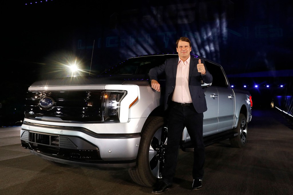 Ford Motor Company's CEO Jim Farley poses next to the electric F-150 Lightning.
