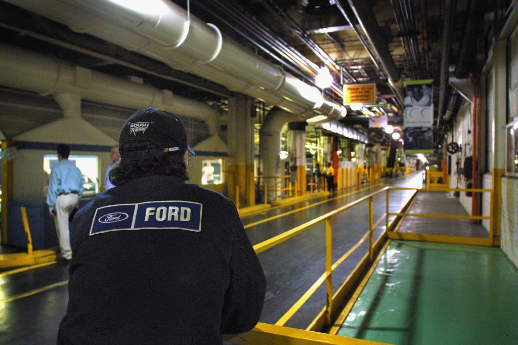 A Ford employee looks down a long aisle at Ford's Dearborn Michigan plant