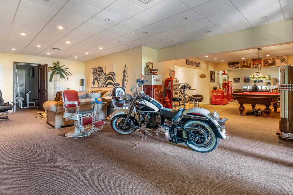 A game room is pictured with a motorcycle and pool table.