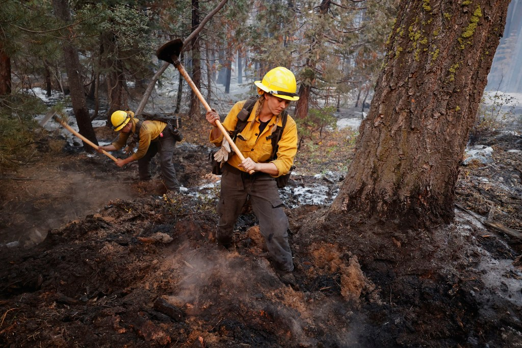 Firefighters Stephanie Lockhart and Dustin Peters of North Tahoe Fire break up smoldering areas after the Caldor Fire moved through the area, in South Lake Tahoe, Calif. on Sept. 1, 2021.