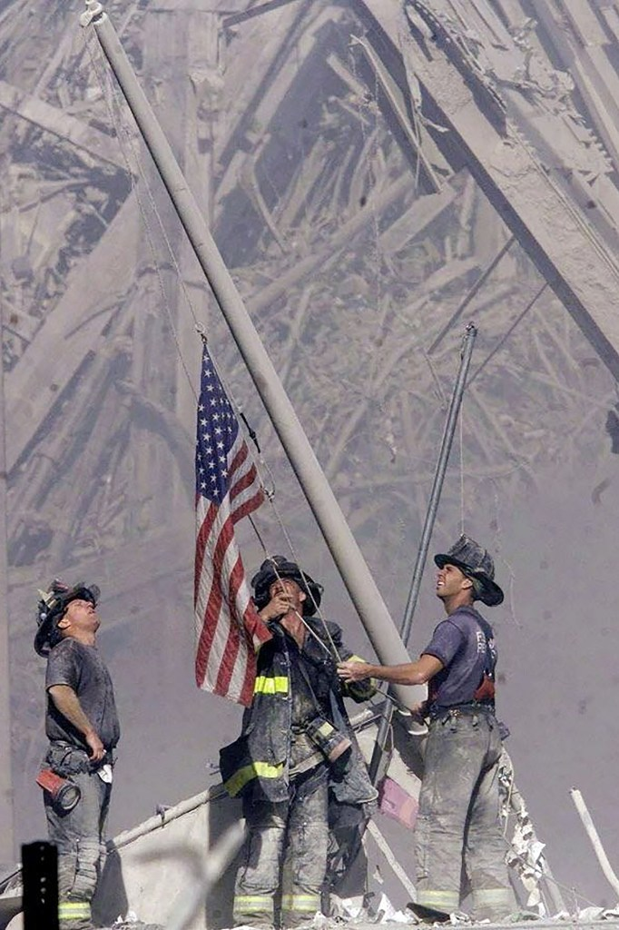 Three NYC firemen, George Johnson and Dan McWilliams and Bill Eisengrein raise an American flag near the rubble of the World Trade Center.