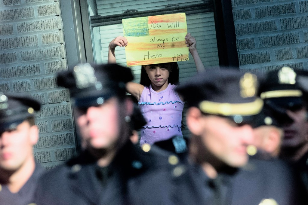Girl holding sign at Port Authority Police Officer Dominick Pezzulo's funeral.