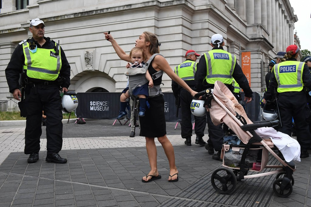 A woman carrying a baby argues with the police as she takes part in an anti-vaccination protest.