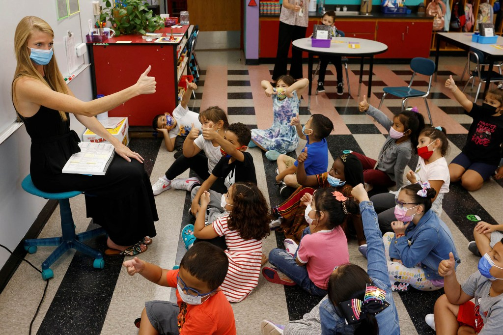 Teacher Emma Rossi works with her first grade students at the Sokolowski School, where students and teachers are required to wear masks because of the coronavirus disease (COVID-19) pandemic, in Chelsea, Massachusetts, U.S., September 15, 2021.