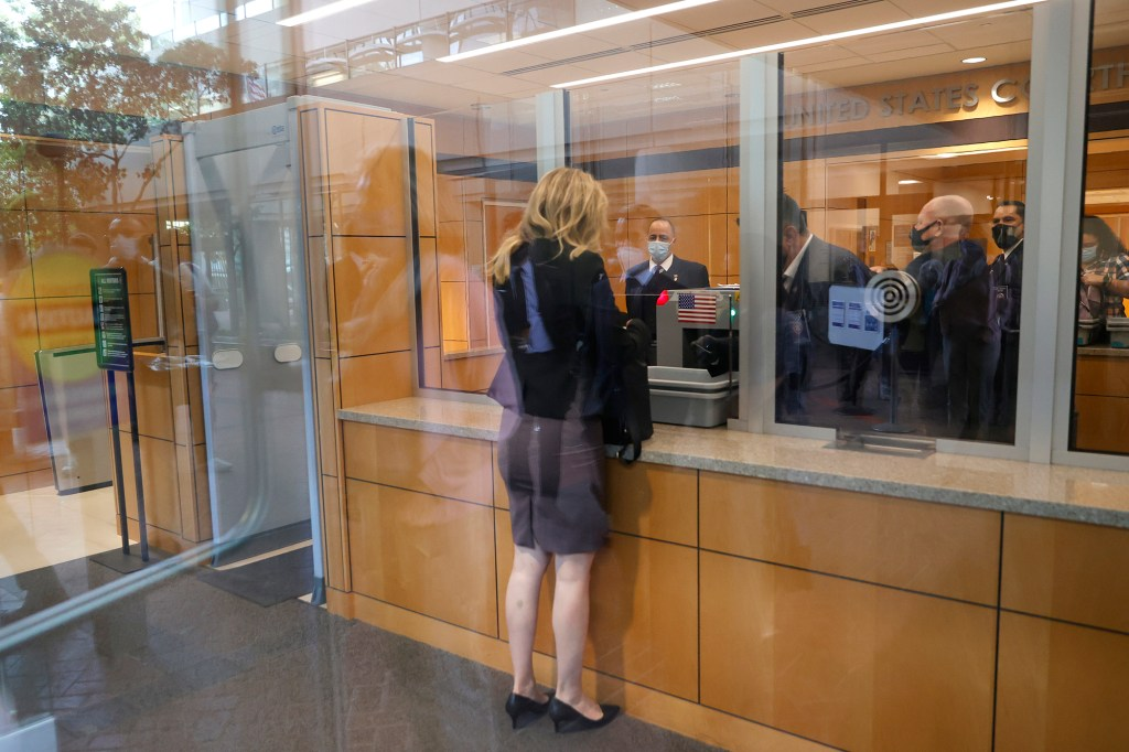 Elizabeth Holmes seen from the rear as she stands in front of plate glass windows at the security desk in a courthouse