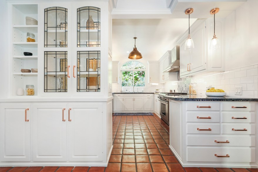 The bright white kitchen has splashes of red and blue.