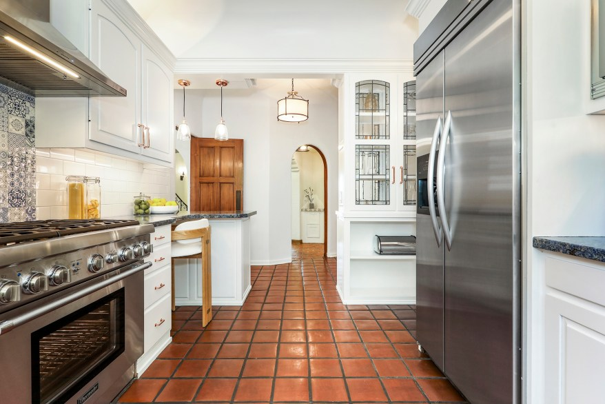 The kitchen has red terracotta floor tiles.
