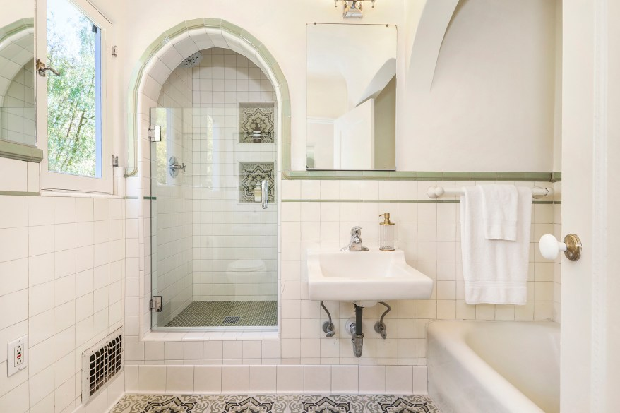 This bathroom with a green pop of color has an arched shower that is raised above the floor.