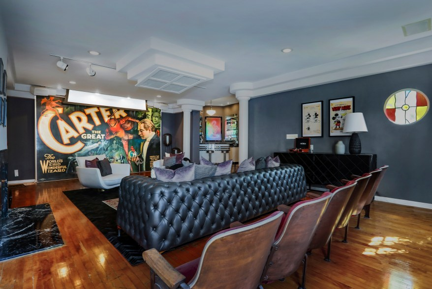 """The room, which can comfortably seat 10, has a stained glass oculus window, a fireplace, a huge """"Carter the Great"""" poster and columns with black marble pedestals."""