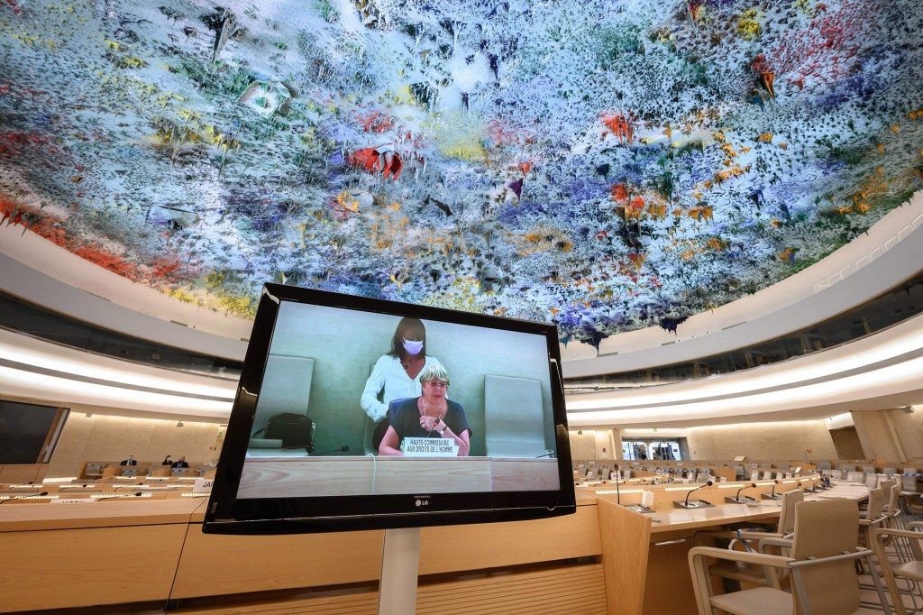 United Nations High Commissioner for Human Rights Michelle Bachelet is seen on a television screen delivering a speech at the opening of a session on the UN Human Rights Council in Geneva on September 13, 2021.