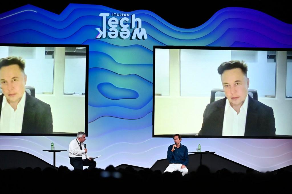 Elon Musk seen on two big screens beneath the words TechWeek as two people sit onstage beneath the screens