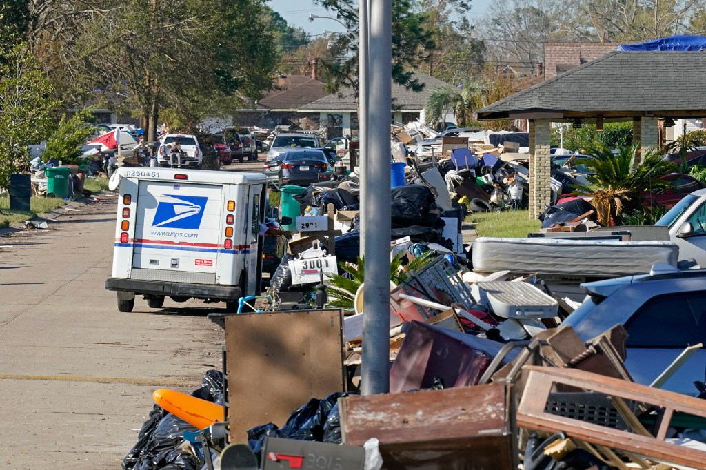 A postal employee delivers mail amidst debris from gutted homes in the aftermath of Hurricane Ida in LaPlace, La., Friday, Sept. 10, 2021.