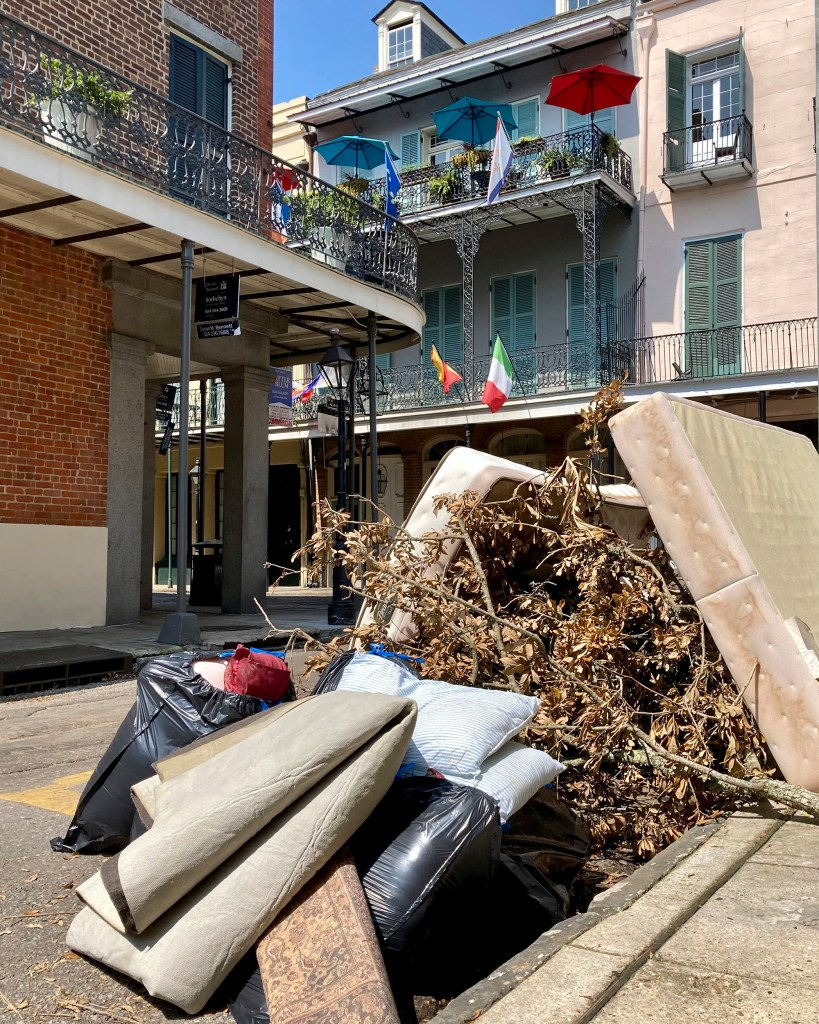 Debris from Hurricane Ida sits on a curb beneath balconies in the French Quarter in New Orleans on Thursday, Sept. 2, 2021.
