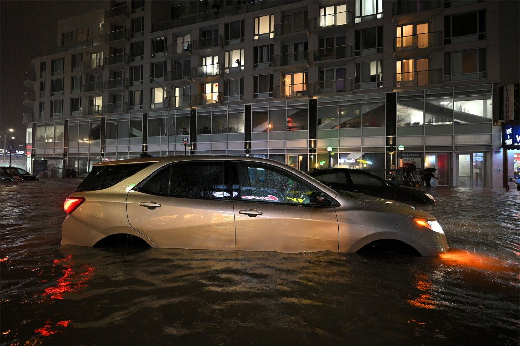A car sits stranded in a flooded street near Queens Boulevard