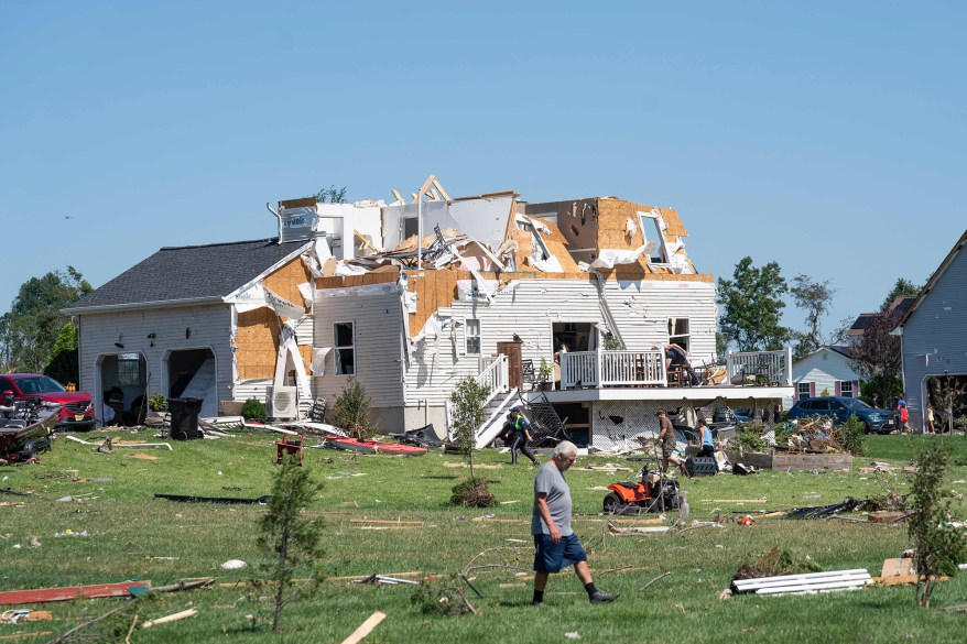A man walks by a home damaged by a tornado in Mullica Hill, New Jersey on September 2, 2021 after record-breaking rainfall brought by the remnants of Storm Ida swept through the area.
