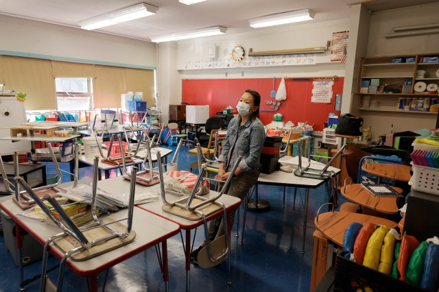 A teacher surveys her classroom in preparation for the upcoming start of school.