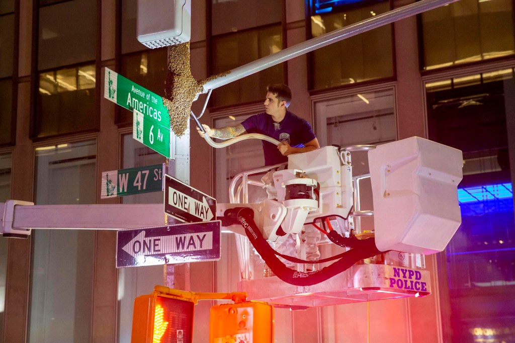 A unit of the NYPD removes a stray beehive from street sign on 6th Ave and W 46th street in midtown, Manhattan