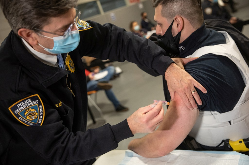 A member of the New York Police Department (NYPD) receives a dose of the Moderna Covid-19 vaccine at Queens Police Academy in the Queens borough of New York, U.S., January 11, 2021.