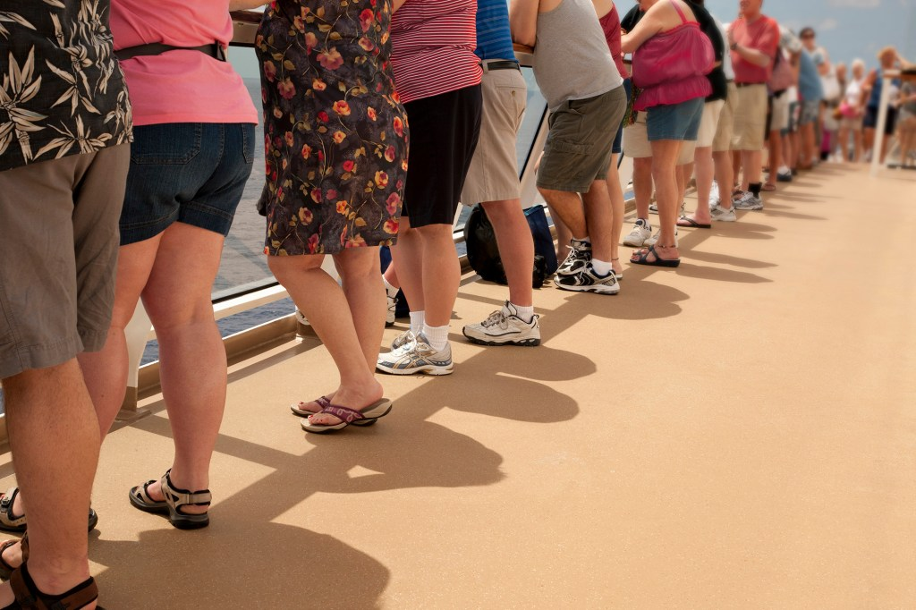 Row of people on railing of a cruise ship, awaiting to get to their vacation destination.