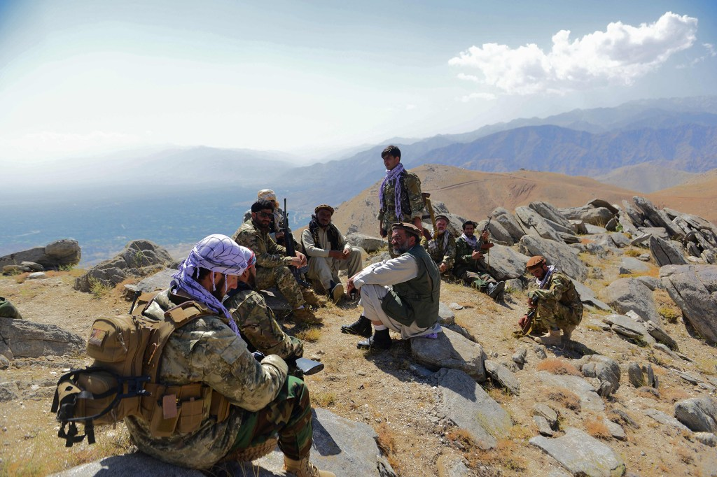 Afghan resistance fighters rest while on a hilltop in Darband in Anaba district of Panjshir province.