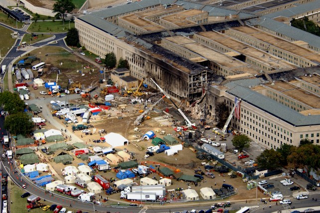 FBI agents, firefighters, rescue workers and engineers are working at the Pentagon crash site on September 14, 2001, where a hijacked American Airlines flight crashed into a building on September 11, 2001.