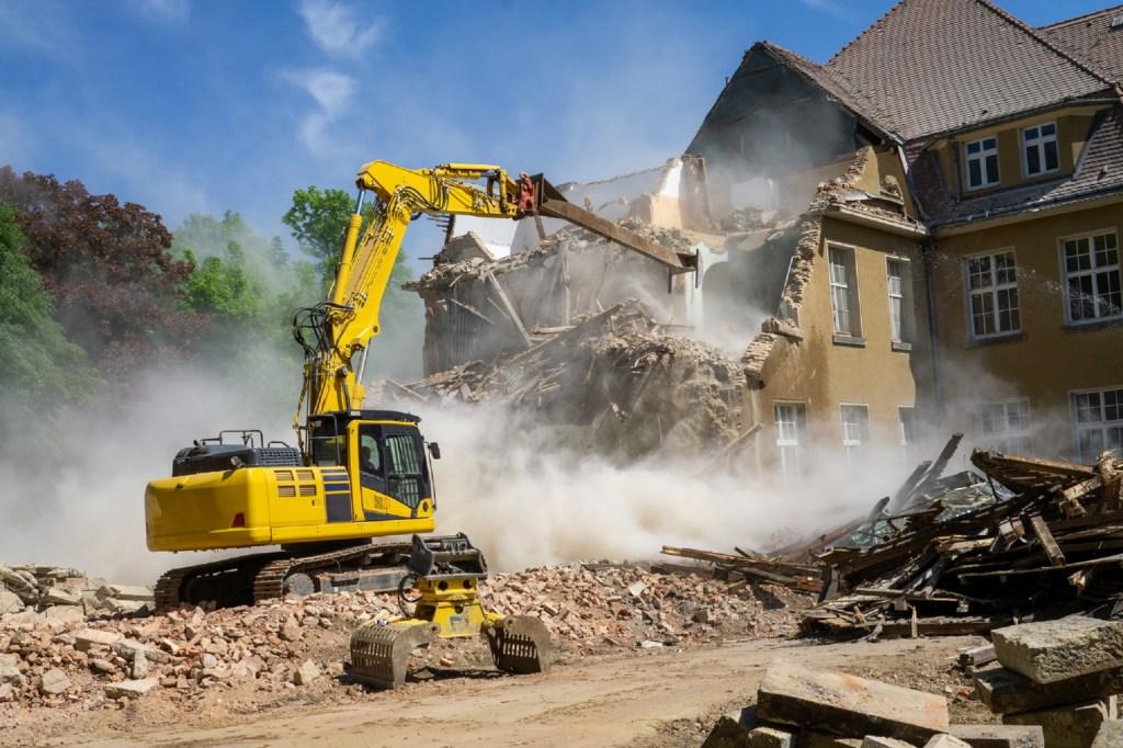 Construction site bulldozer demolishing house for reconstruction.
