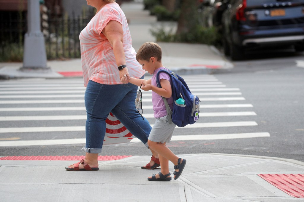 A student walks to school on the first day of New York City