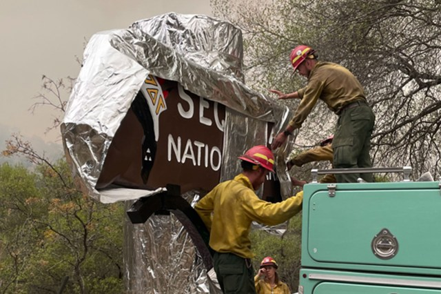Firefighters wrap the Sequoia National Forest Sign with fire-resistant structural wrap to protect it from the KNP Complex Fire.