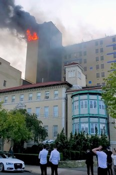 Bystanders watch as the flames rage at St. John's hospital.