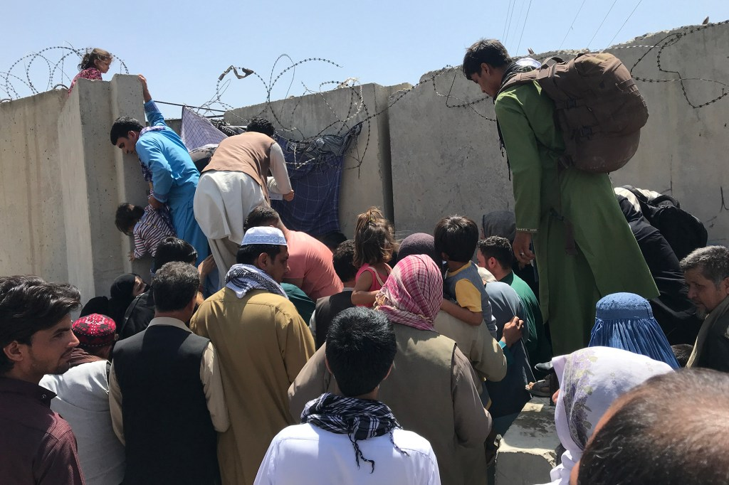 People struggle to cross the boundary wall of Hamid Karzai International Airport to flee the country after rumors that foreign countries are evacuating people even without visas.