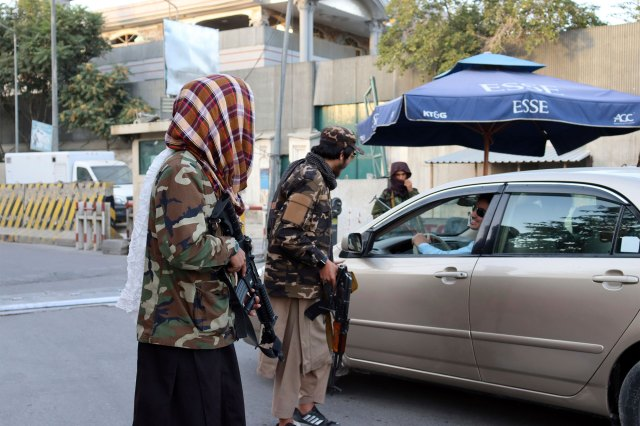 Taliban fighters speaking with a driver at a checkpoint in Kabul on August 25, 2021.