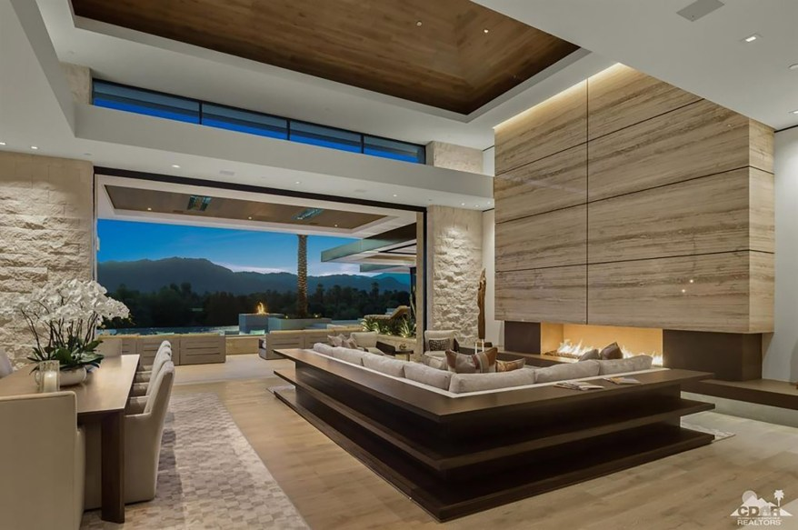 This living room has a floor-to-ceiling fireplace and a trey ceiling.
