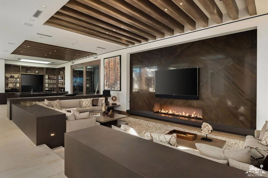 This beamed-ceiling room has a fireplace.