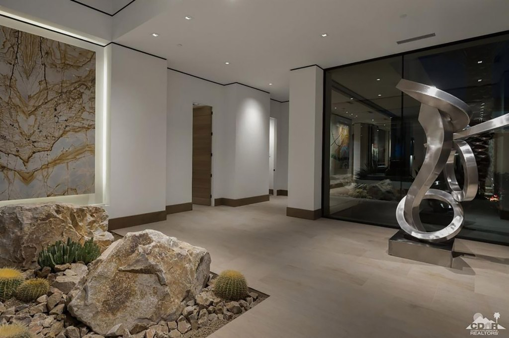 Listing photos show a metal sculpture and rocky indoor terrain.