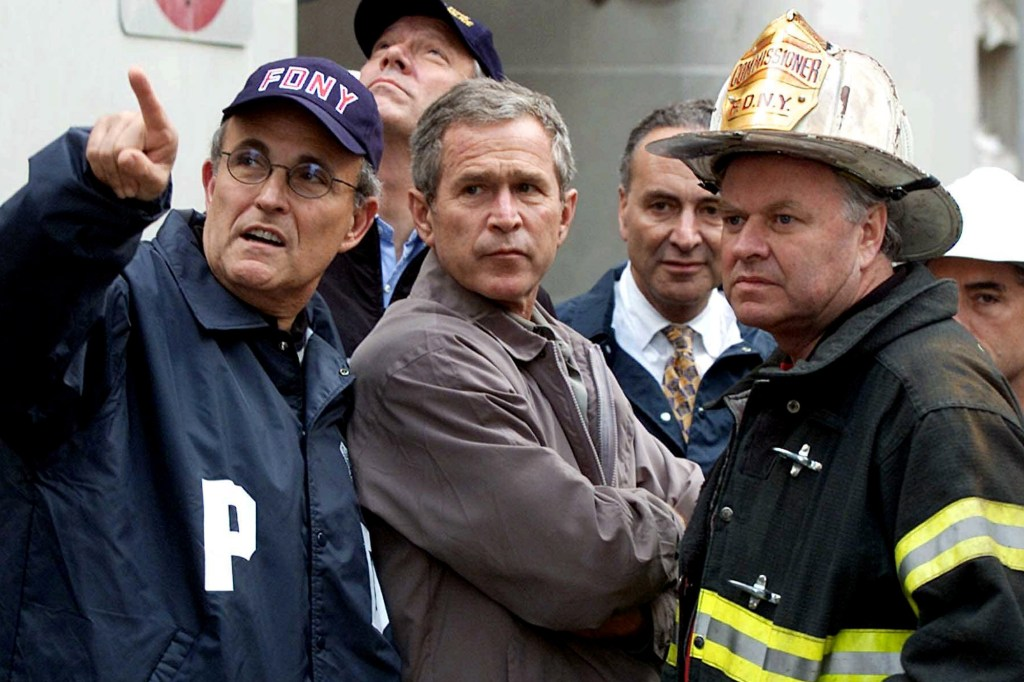 President Bush, center, former New York City Mayor Rudolph Giuliani, left, and New York Gov. George Pataki, second from left, Sen. Charles Schumer, D-N.Y., second from right, and former New York City Fire Commissioner Thomas Van Essen, right, look toward the fallen buildings during a tour of the World Trade Center, in this Sept. 14, 2001.