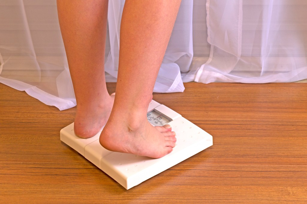 Woman steps on a scale to weigh herself.