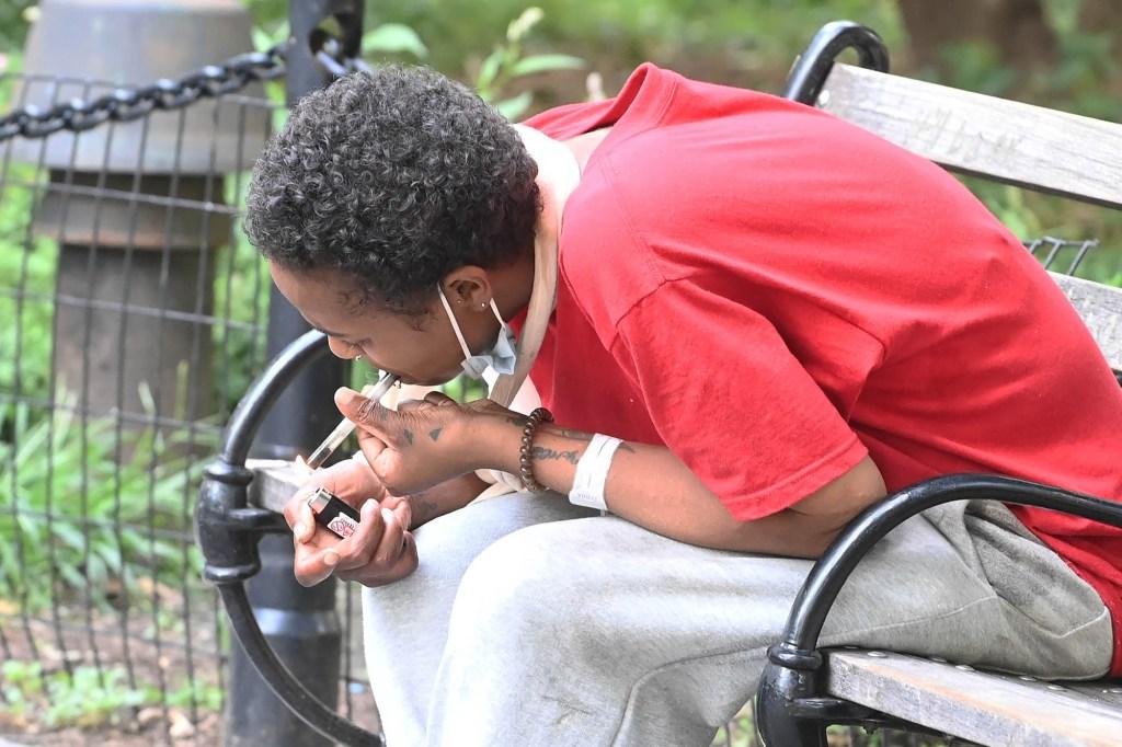 Woman smokes crack in Washington Square Park.