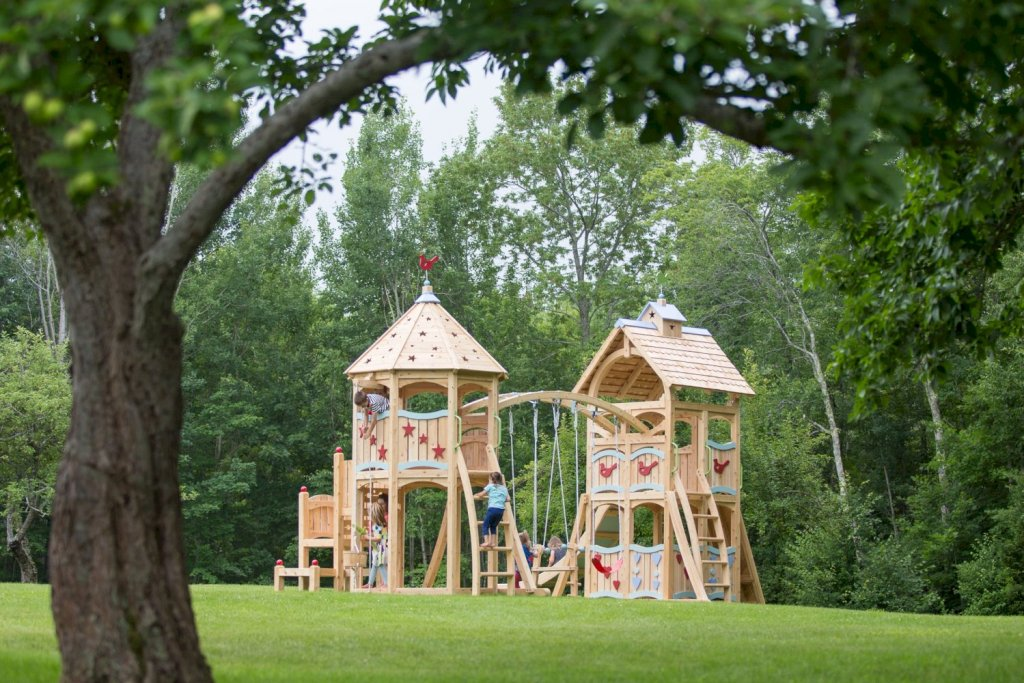 The wooden castle, one of Cedarworks' Serendipity models, has two turrets and an grand arch with two traditional poly swings and a horse-like swing underneath.