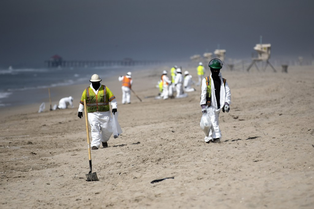 Workers cleaning up tar from Huntington Beach after the oil spill on October 4, 2021.