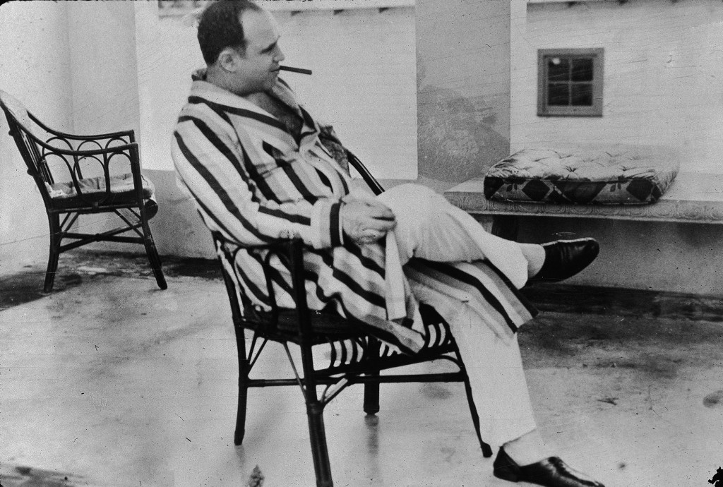 """American gangster Al Capone, who inspired the film """"Scarface"""" relaxes in his vacation home im Miami, Florida in 1930. Capone smokes a cigar and wears a striped dressing gown and slippers."""